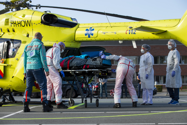 The photo shows a COVID-19 patient is carried into a helicopter.