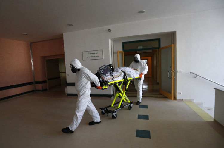 The photo shows health care workers transport a COVID-19 patient.