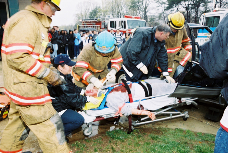 The photo shows first responders at a crash scene.
