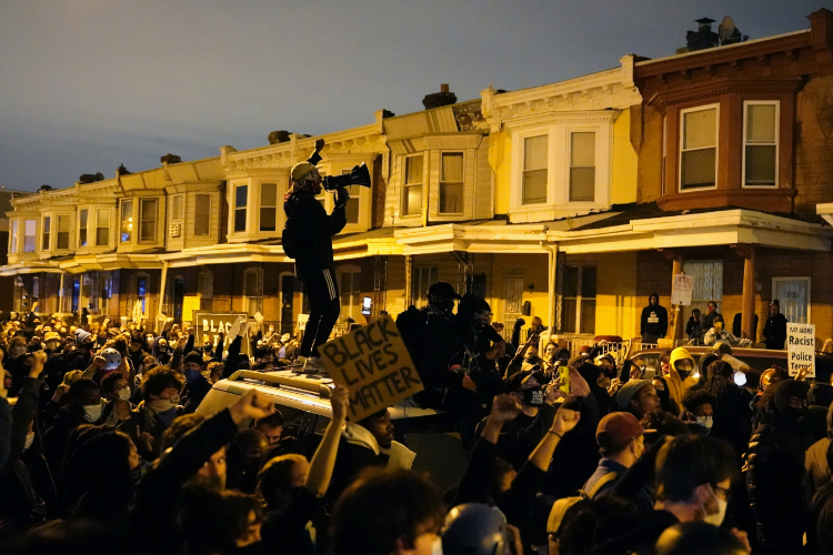 The photo shows protesters confronting police in Philadelphia.
