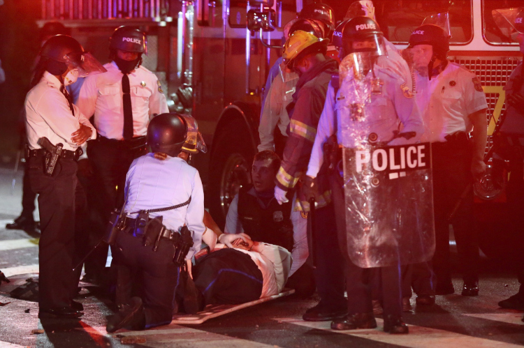 The photo shows a police officer on a stretcher.