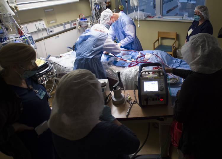 Members of the 59th Medical Wing Extracorporeal Membrane Oxygenation transport team connect a patient to an ECMO system for transport.