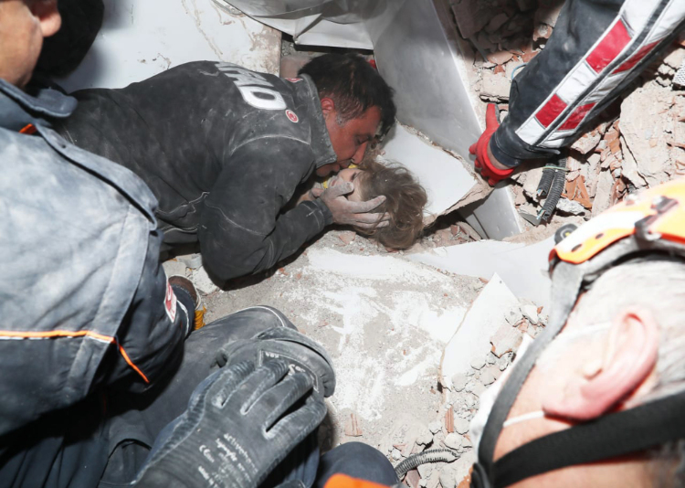 A rescuer kissed a young girl found in the rubble.