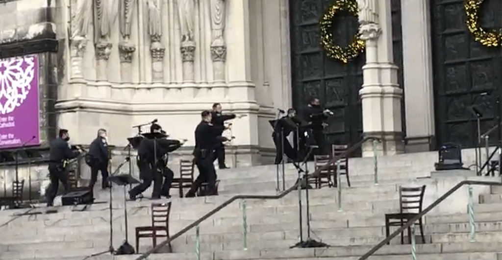 New York police officers move in on the scene of a shooting at the Cathedral Church of St. John the Divine, Sunday, Dec. 13, 2020, in New York.