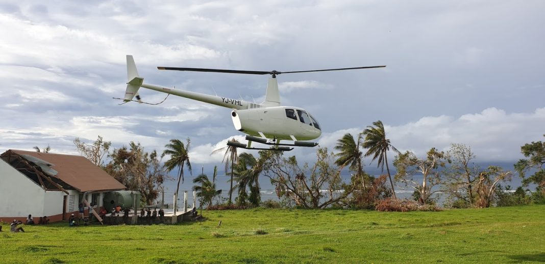 The rescue helicopter flying over a damaged building in Vanuatu.