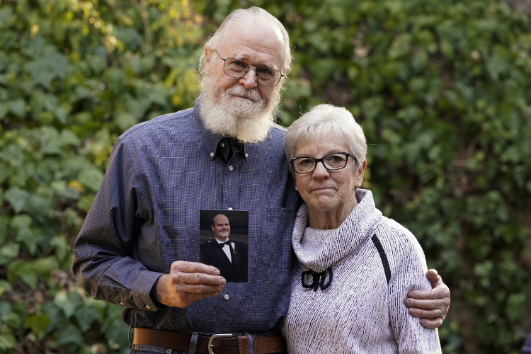 Clark McIlvain and Kathleen McIlvain hold a photo of their son, Charles McIlvain.