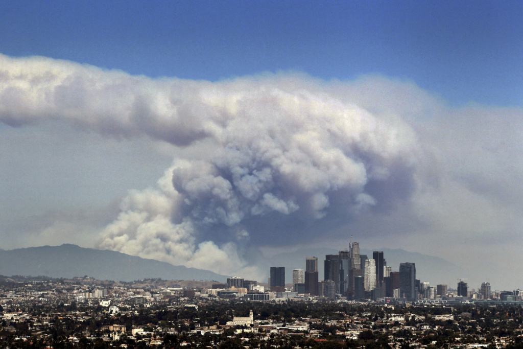 In this Monday, June 20, 2016 file photo, smoke from wildfires burning in Angeles National Forest fills the sky behind the Los Angeles skyline.