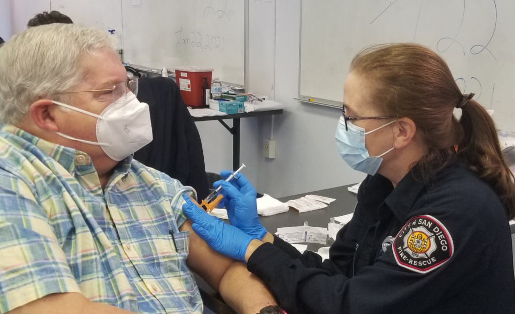 JEMS Editor Emeritus A.J. Heightman is vaccinated by San Diego Fire Rescue Paramedic Program Clinical Coordinator Carolyn Gates.