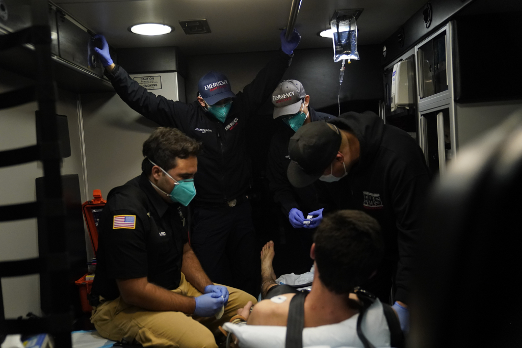 Emergency medical workers Trenton Amaro, from left, Joshua Hammond, Thomas Hoang and Charles Navarro are crammed in an ambulance as they treat a patient.