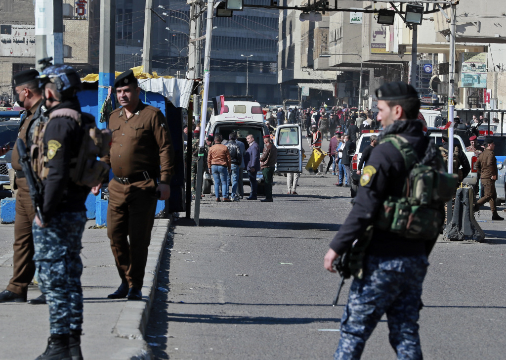 Security forces work at the site of a deadly bomb attack in Baghdad, Iraq, Thursday, Jan. 21, 2021. Iraq's military said twin suicide bombings at the Bab al-Sharqi commercial area in central Baghdad Thursday ripped through the busy market killing over two dozen and wounding over 70, with some in serious condition.
