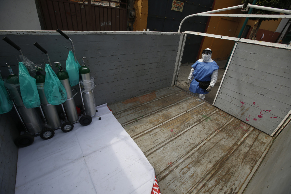 City worker Carlos Ruiz loads tanks of oxygen for COVID-19 patients, in the Iztapalapa borough of Mexico City, Friday, Jan. 15, 2021. The city offers free oxygen refills for COVID-19 patients.