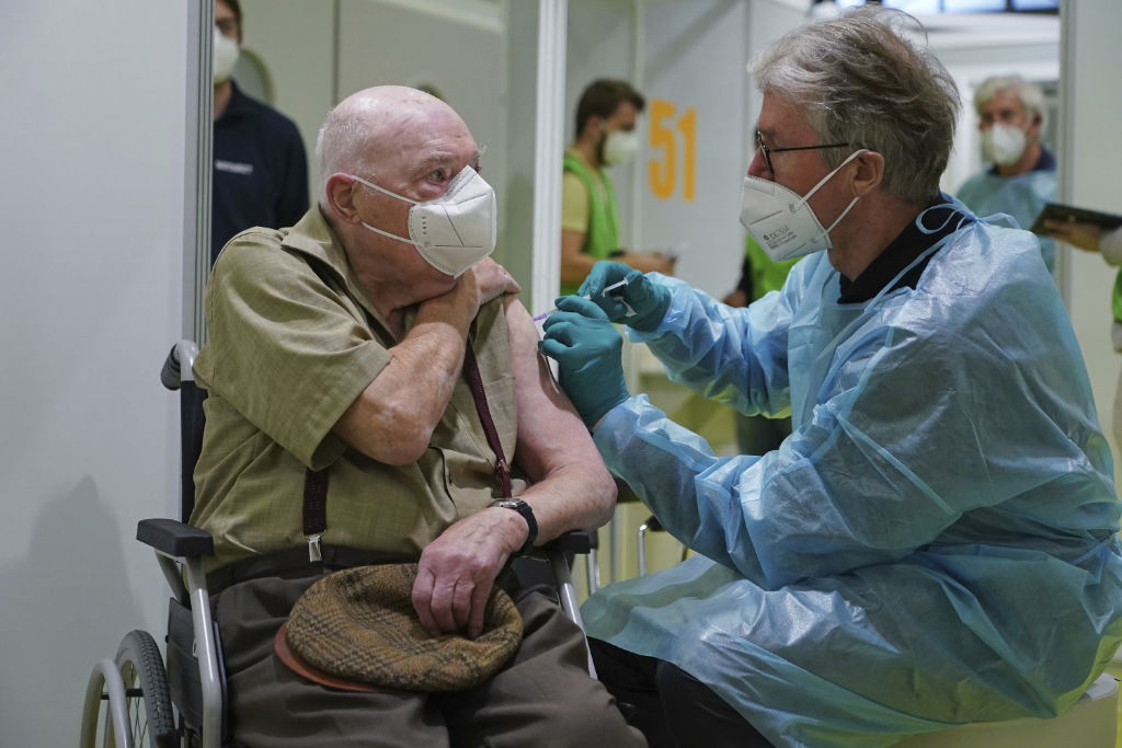 A doctor inoculates Herri Rehfeld, 92, against the new coronavirus with the Pfizer/BioNTech vaccine at the vaccination center at the Messe Berlin trade fair grounds on the center's opening day in Berlin, Germany, Monday, Jan. 18, 2021.