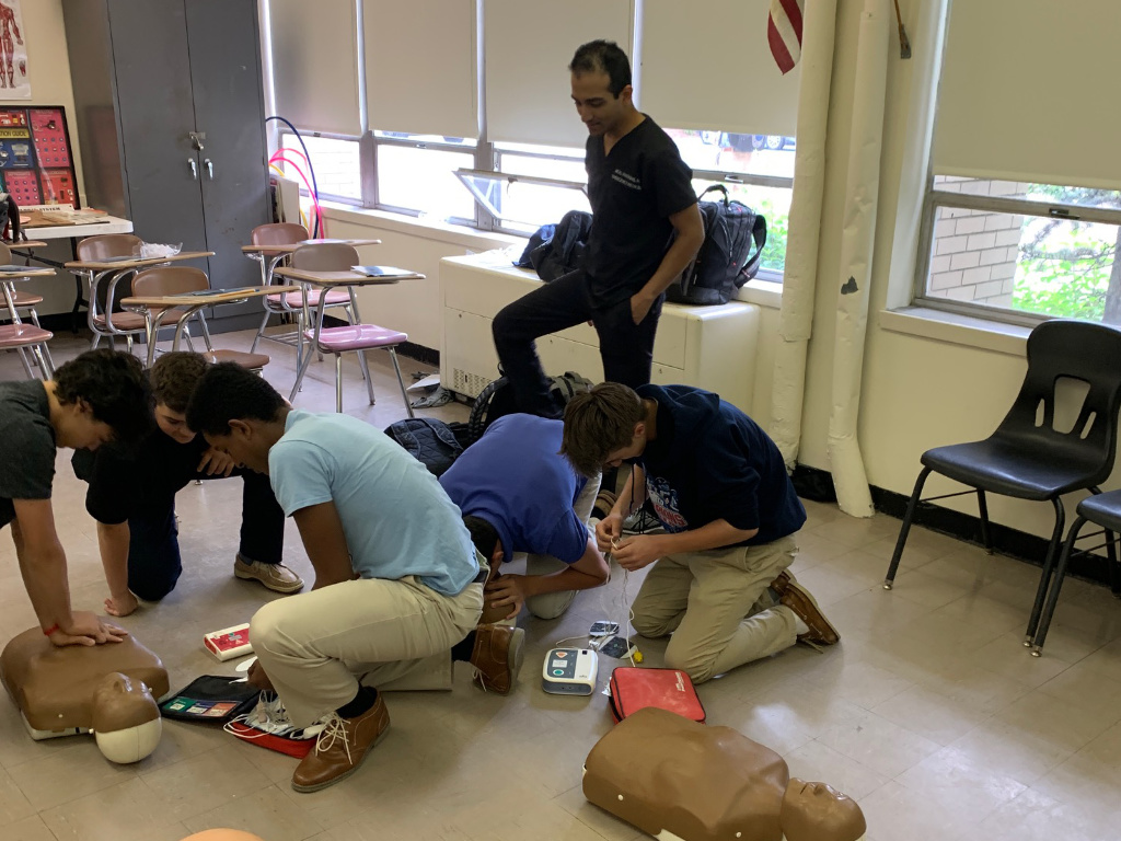 Neal Madhani, MD, instructs students on proper CPR and AED use during the hands-on simulation part of the AHA Heartsaver course.