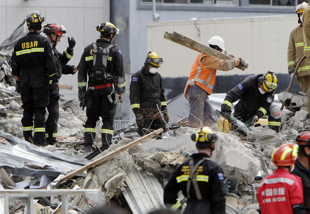 In this Feb. 26, 2011, file photo, recovery workers sift through the rubble of the earthquake-damaged CTV building in Christchurch, New Zealand.