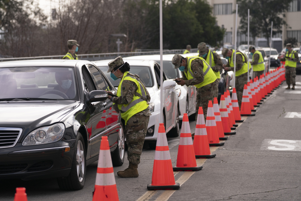 Members of the National Guard help motorists check in at a federally-run COVID-19 vaccination site set up on the campus of California State University of Los Angeles in Los Angeles, Tuesday, Feb. 16, 2021.