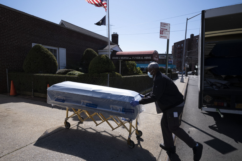 In this Friday, March 27, 2020 file photo, William Samuels delivers caskets to the Gerard Neufeld Funeral Home during the coronavirus pandemic in the Queens borough of New York.