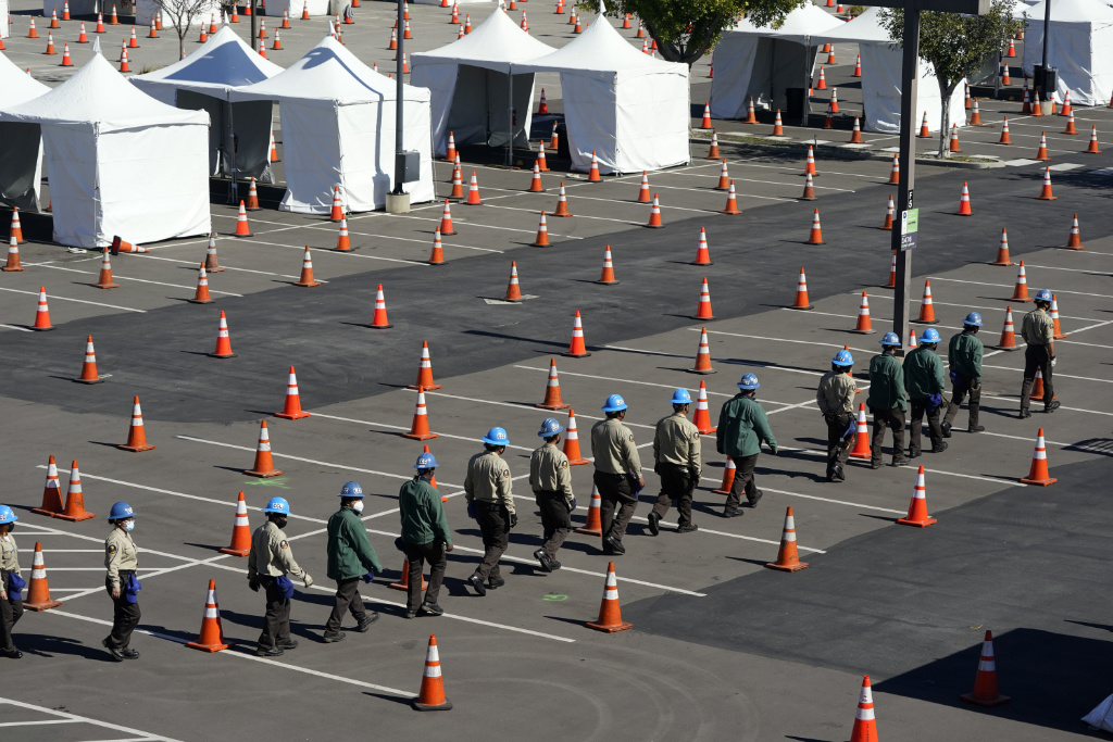 Members of the California Conservation Corps line up to help with the setup of a new federal COVID-19 vaccination center on the campus of the California State University Los Angeles Friday, Feb. 12, 2021, in Los Angeles.