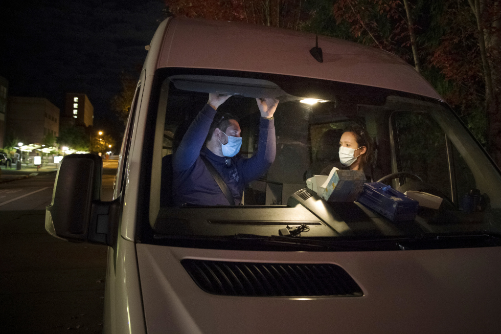 In this Oct. 2020 photo, Crisis Workers, Emergency Medical Technicians (EMTs), Henry Cakebread and Ashley Barnhill-Hubbard with CAHOOTS, a mental health crisis intervention program, discuss their last encounter during their night shift in Eugene, Ore.