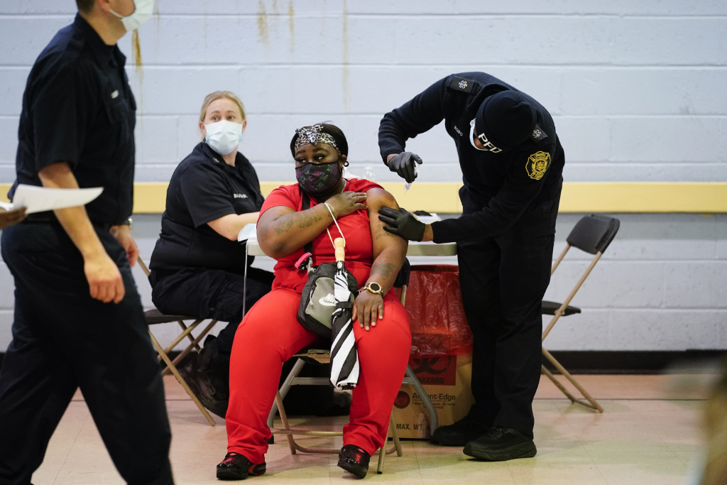 In this March 26, 2021, file photo, a member of the Philadelphia Fire Department administers the Johnson & Johnson COVID-19 vaccine to a woman at a vaccination site setup at a Salvation Army location in Philadelphia.