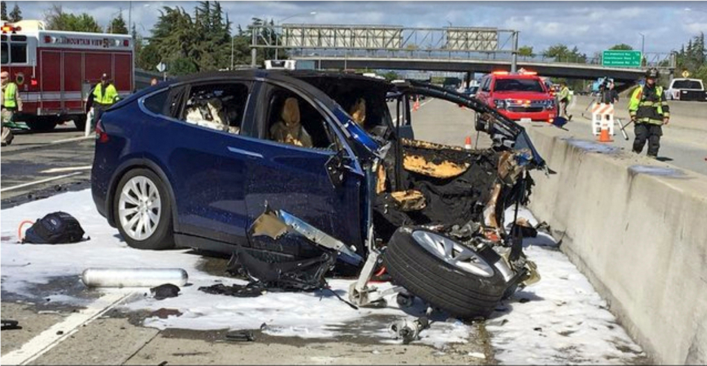 In this March 23, 2018, file photo provided by KTVU, emergency personnel work a the scene where a Tesla electric SUV crashed into a barrier on U.S. Highway 101 in Mountain View, Calif.