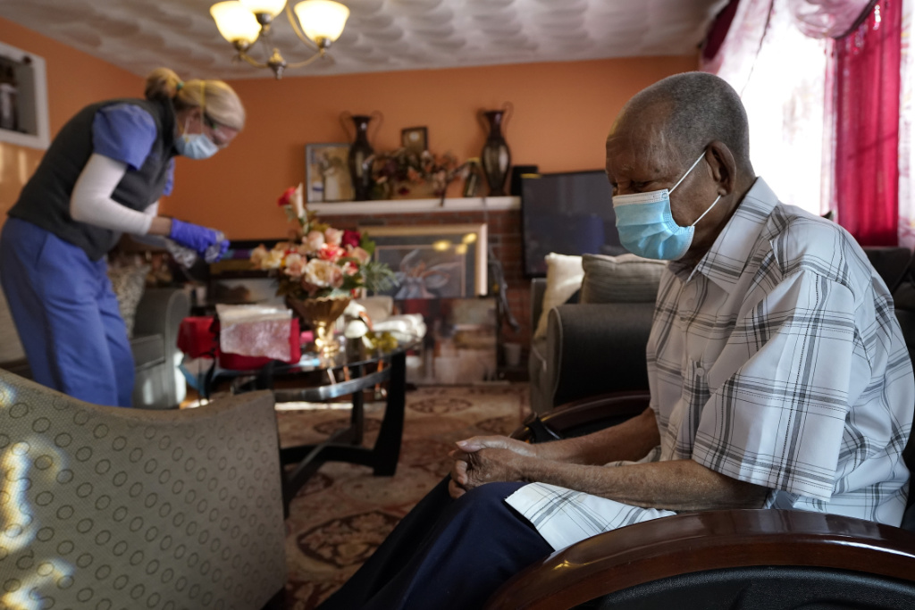 Edouard Joseph, 91, right, clasps his hands as geriatrician Megan Young, left, prepares to give him a COVID-19 vaccination at his home in the Mattapan neighborhood of Boston.