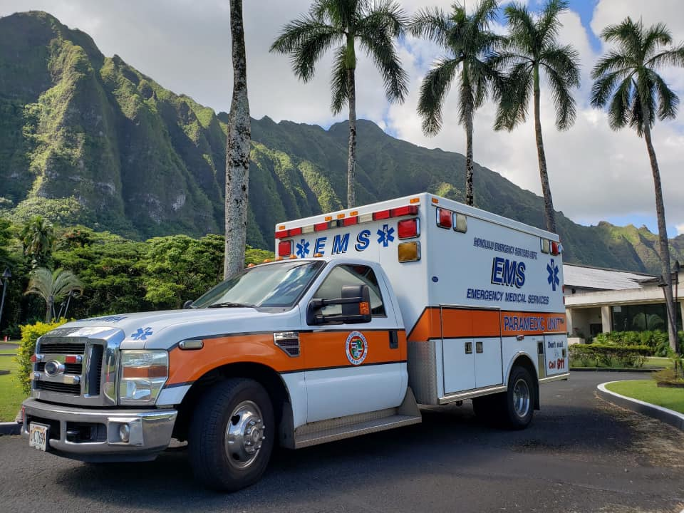 The photo shows a Honolulu Emergency Medical Services ambulance near palm trees.