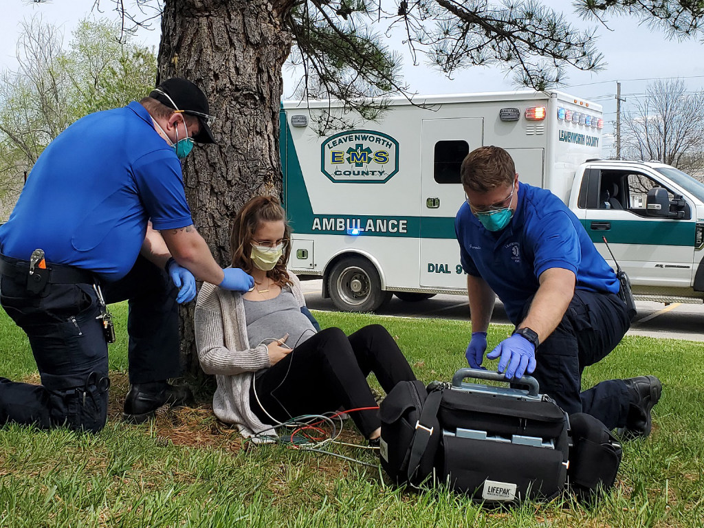 A woman is propped up against a tree while paramedics treat her.
