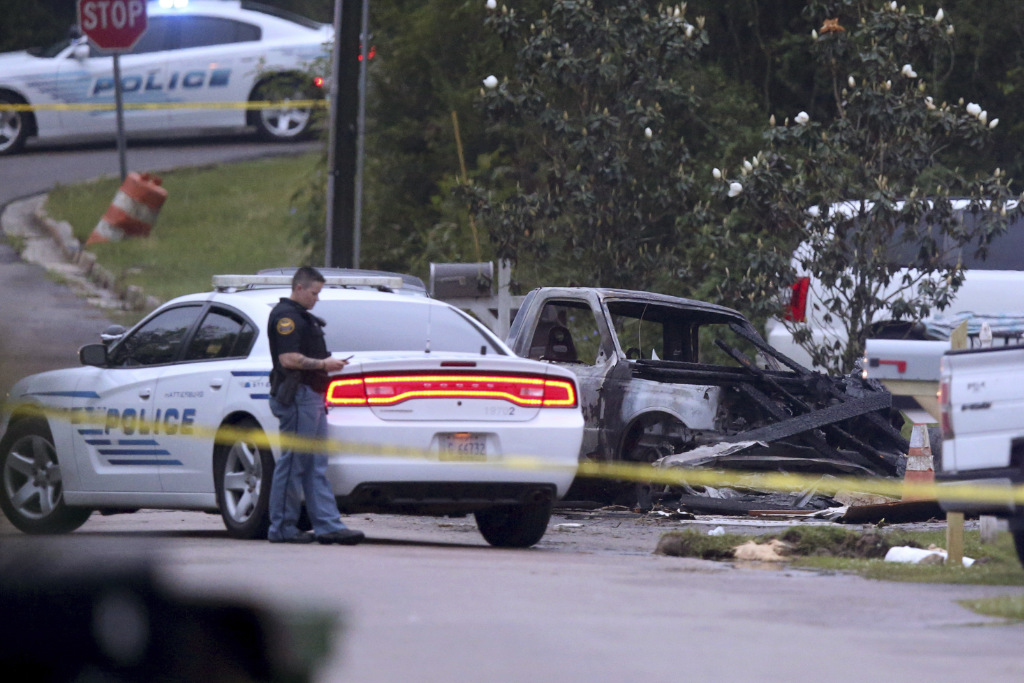 Hattiesburg police surround a burned automobile and a damaged home after a small plane crashed late Tuesday night in Hattiesburg, Miss., Wednesday May 5, 2021.